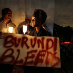 "A Burundian expatriate holds a placard reading ""Burundi bleeds"" during a candlelight vigil held in December. (Dai Kurikawa/European Pressphoto Agency)"