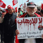 "A Tunisian protester in March 2015 carrying a poster speaks that says ""no fear and no terror"" and reaffirms ""Tunisia will be protected by its people"". The years immediately following the 2011 revolution have been tense years as extremists mounted violent attacks on security and military personnel but gradually expanded this to political activists, civilians and tourists, and diplomatic property."